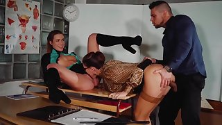 Two horny sluts increased by a handsome guy are having a great sex time, while in the classroom